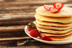 Delicious pancakes with strawberry on brown wooden background. Stock Photo