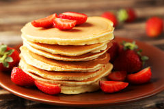 Delicious pancakes with strawberry on brown wooden background. Stock Photography