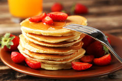 Delicious pancakes with strawberry on brown wooden background. Royalty Free Stock Photos