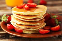 Delicious pancakes with strawberry on brown wooden background. Stock Image