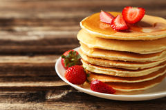 Delicious pancakes with strawberry on brown wooden background. Royalty Free Stock Photo