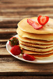 Delicious pancakes with strawberry on brown wooden background. Royalty Free Stock Images
