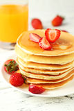 Delicious pancakes with strawberry on white wooden background. Royalty Free Stock Images