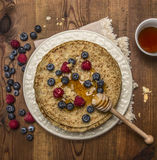 Delicious pancakes on a white plate with napkin  with honey and honey spoon  almonds blueberries and raspberries and a cup of tea Stock Image