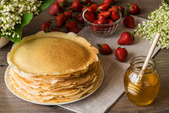Delicious pancakes on wooden table with strawberries and honey Royalty Free Stock Photos