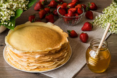 Delicious pancakes on wooden table with strawberries and honey Stock Images