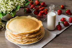 Delicious pancakes on wooden table with strawberries and milk Royalty Free Stock Photos