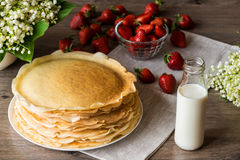 Delicious pancakes on wooden table with strawberries and milk Stock Photo