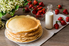 Delicious pancakes on wooden table with strawberries and milk Stock Photos