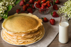 Delicious pancakes on wooden table with strawberries and milk Royalty Free Stock Image