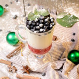 Delicious parfait dessert with bilberry, milk souffle and jello layers. Frozen treat in a glass on rustic wooden. Delicious parfait dessert with bilberry berries Royalty Free Stock Photo
