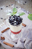 Delicious parfait dessert with bilberry, milk souffle and jello layers. Frozen treat in a glass on rustic wooden. Delicious parfait dessert with bilberry berries Royalty Free Stock Photos