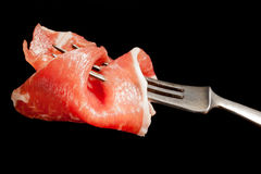 Delicious parma ham on fork isolated. Royalty Free Stock Photos