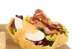 Delicious parmigiano cheese basket. Delicious parmigiano cheese basket stuffed with fresh salad, egg and bacon on white background. Culinary gourmet eating Stock Photo
