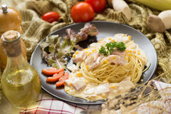 Delicious pasta carbonara with bacon and parmesan in a black bow. L. homemade food style Royalty Free Stock Photo