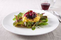 Delicious pasta dish. With greens and blood sausage on top Stock Photo