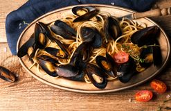Delicious pasta with seafood and sliced cherry tomatoes on metal plate royalty free stock image