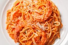Delicious pasta spaghetti with shrimps, tomato sauce, cheese on a white plate Stock Photo
