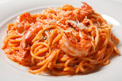 Delicious pasta spaghetti with shrimps, tomato sauce, cheese on a white plate Stock Photos