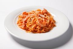 Delicious pasta spaghetti with shrimps, tomato sauce, cheese on a white plate Royalty Free Stock Photo