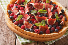 Delicious pastry: tart with fresh figs, raspberries and blueberr Stock Photo
