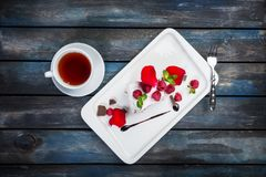 Delicious Pavlova cake with a cup of tea. Fresh raspberries on a white plate with rose petals. Top view. Beautiful. Delicious Pavlova cake with a cup of tea Royalty Free Stock Images