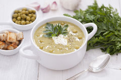 A delicious pea cream with aromatic spices on a wooden table. Stock Photo