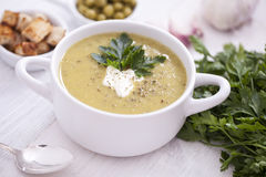 A delicious pea cream with aromatic spices on a wooden table. Royalty Free Stock Photo