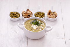 A delicious pea cream with aromatic spices on a wooden table. Stock Images