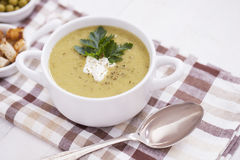 A delicious pea cream with aromatic spices on a wooden table. Royalty Free Stock Photography