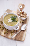 A delicious pea cream with aromatic spices on a wooden table. Stock Image