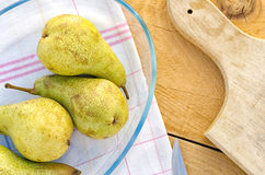 Delicious pears in glass bowl on old kitchen table Royalty Free Stock Photo