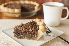 Delicious Pecan Pie with Coffee. Slice of pecan pie one a white plate with cup of coffee royalty free stock image