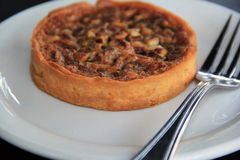Delicious pecan tart on white plate with silverware Stock Photography