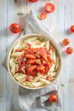 Delicious penne bolognese with bacon and herbs Stock Photos