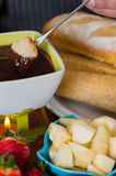 Delicious piece of bread in a metal stick covered with chocolate fondue inside of a white bowl with assorted fruits in. Delicious kiwi and a piece of bread in a Stock Image