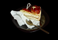Delicious piece of cake on black background. Delicious piece of cake on black plate, isolated black background Royalty Free Stock Images