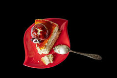 Delicious piece of cake on black background. Delicious piece of cake on red saucer, isolated black background with clipping path Royalty Free Stock Photography