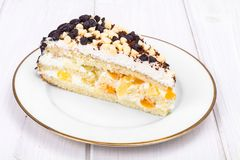 Delicious piece of cake with fruit, whipped cream and chocolate drops. Studio Photo Stock Images