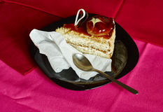 Delicious piece of cake on red and pink background. Delicious piece of cake on black plate with red and pink background Royalty Free Stock Photos