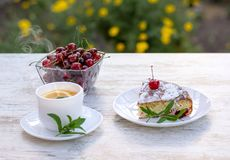 A piece of cherry pie and hot tea with lemon and mint. A delicious piece of cherry pie on a white plate and a white cup of hot tea with lemon and mint. close-up stock photos