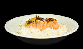 Delicious piece of salmon on a bed of long grained rice. In a deep plate towards black Stock Photo