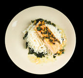 Delicious piece of salmon on a bed of rice, and spinach. Delicious piece of salmon on a bed of long grained rice, and spinach, on a plate towards black Stock Photo