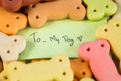 Delicious Pile of dog biscuits in the shape of a bone and short note. Stock Photography