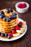 Delicious pile of hot homemade pancakes with fresh raspberries. And blueberries drizzled with maple syrup Stock Images