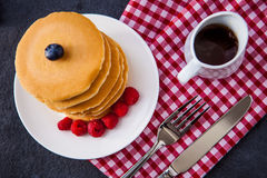 Delicious pile of hot homemade pancakes with fresh raspberries. And blueberries and a jug of maple syrup Royalty Free Stock Photos