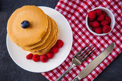 Delicious pile of hot homemade pancakes with fresh raspberries Stock Images