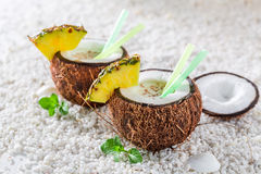 Delicious pinacolada in coconut with pineapple and mint leaves Stock Images