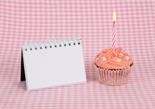 Delicious pink birthday cupcake with candle Stock Images