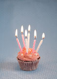 Delicious pink birthday cupcake with candles Royalty Free Stock Images